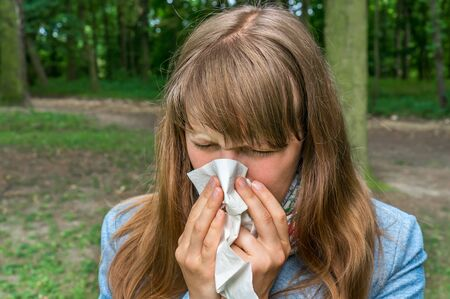 Woman with flu or allergy symptoms sneezing in park