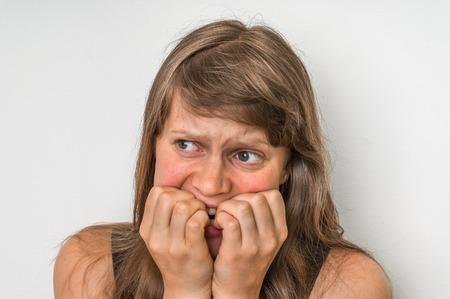 Zenuwachtige vrouw bijten haar nagels geïsoleerd op wit Stockfoto