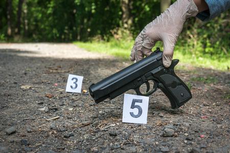 Investigator collects evidence (pistol) - crime scene investigation