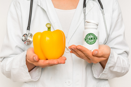 Female doctor compare pile of pills with fresh yellow pepper - healthy food concept
