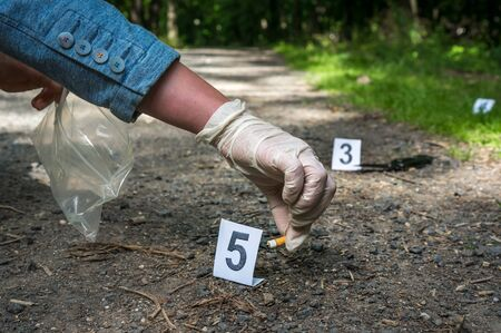 Investigator collects evidence (cigarette butt) - crime scene investigation 스톡 콘텐츠