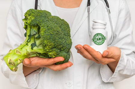 Female doctor compare pile of pills with fresh broccoli - healthy food concept