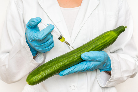 GMO scientist injecting liquid from syringe into cucumber - genetically modified food concept