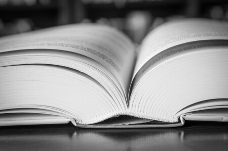 Black and white open book on the table in a library - close up