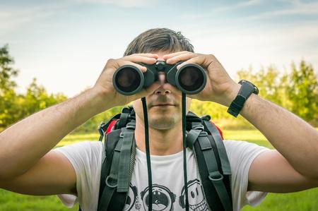 Reisendmann mit rotem rucksack schaut durch ferngläser wandern