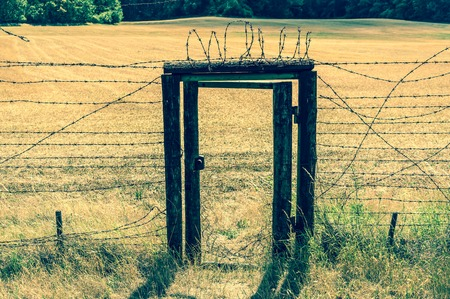 demarcation: Remains of iron curtain with door inside wire fence in Czech republic - retro style