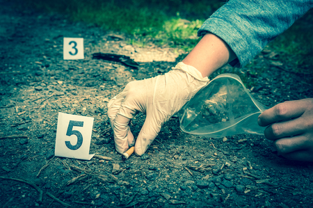 Investigator collects evidence (cigarette butt) - crime scene investigation - retro style Stock Photo