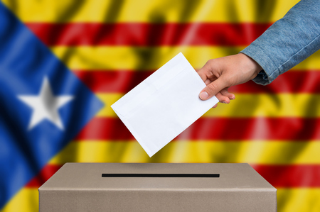 Statute of Autonomy of Catalonia - voting at the ballot box. The hand of woman putting her vote in the ballot box. Catalan flag on background.