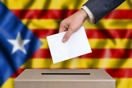 Statute of Autonomy of Catalonia - voting at the ballot box. The hand of man putting her vote in the ballot box. Catalan flag on background.