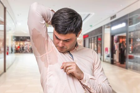 Young man with sweating under armpit in shopping center