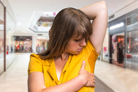 Young woman with sweating under armpit in shopping center Stock Photo