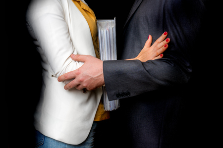 Man touching womans elbow isolated on black - sexual harassment in business office Stok Fotoğraf
