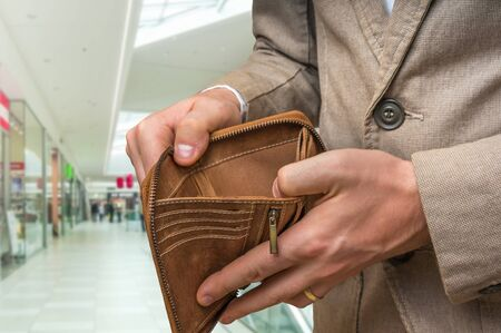 he: Businessman holding an empty wallet in shopping centre, he hasnt money