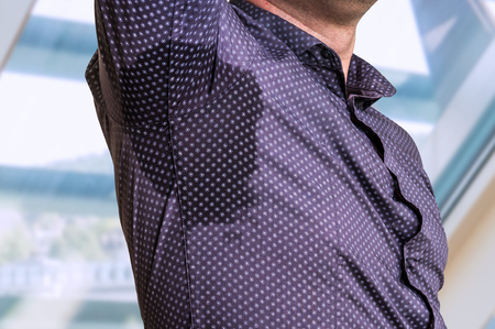 Young man with sweating under armpit in business office Stock Photo