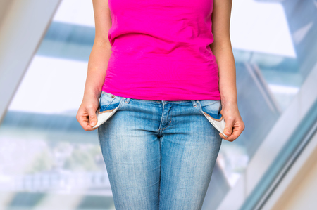 Young woman pulling out empty pockets, she hasn't money Stock Photo