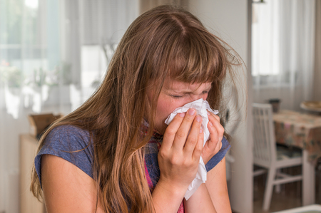 Sick woman with flu or cold sneezing into handkerchief at home Stock Photo