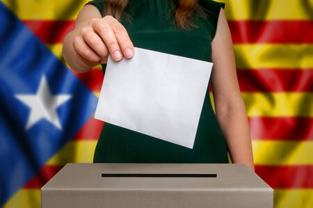 Election in Catalonia - voting at the ballot box. The hand of woman putting her vote in the ballot box. Flag of Catalonia on background.