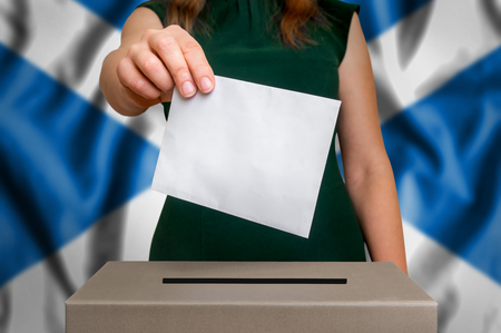 Election in Scotland - voting at the ballot box. The hand of woman putting her vote in the ballot box. Flag of Scotland on background. Zdjęcie Seryjne