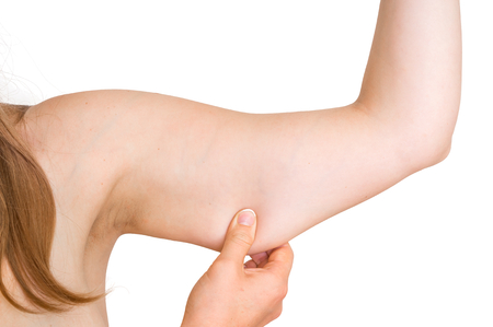 Woman is testing her muscle under her arm - healthcare fit and diet concept