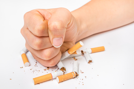Human fist and pile of broken cigarettes, nicotine addiction - stop smoking concept