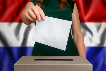 Election in Netherlands - voting at the ballot box. The hand of woman putting her vote in the ballot box. Flag of Netherlands on background.