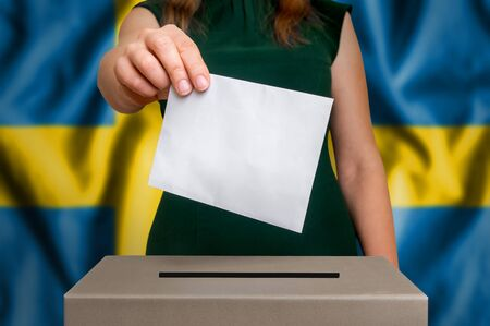 Election in Sweden - voting at the ballot box. The hand of woman putting her vote in the ballot box. Flag of Sweden on background.