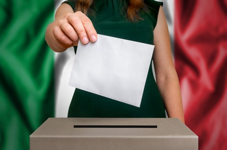 Election in Italy - voting at the ballot box. The hand of woman putting her vote in the ballot box. Flag of Italy on background. Imagens