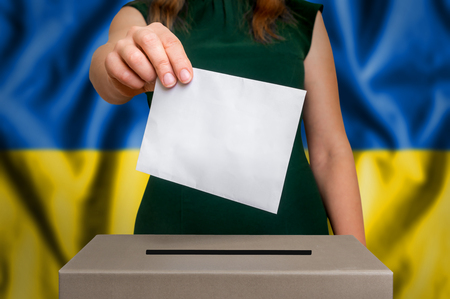 Election in Ukraine - voting at the ballot box. The hand of woman putting her vote in the ballot box. Flag of Ukraine on background. Stock Photo