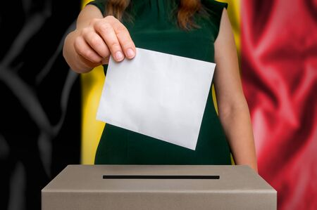 Election in Belgium - voting at the ballot box. The hand of woman putting her vote in the ballot box. Flag of Belgium on background. Stock Photo