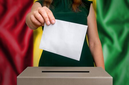 Election in Guinea - voting at the ballot box. The hand of woman putting her vote in the ballot box. Flag of Guinea on background.