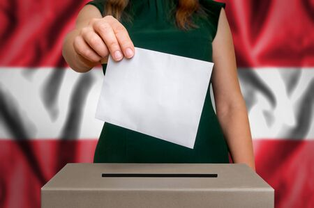 Election in Austria - voting at the ballot box. The hand of woman putting her vote in the ballot box. Flag of Austria on background.