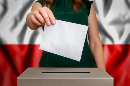 Election in Poland - voting at the ballot box. The hand of woman putting her vote in the ballot box. Flag of Poland on background. Stock Photo