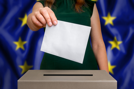Election in European Union - voting at the ballot box. The hand of woman putting her vote in the ballot box. Flag of EU on background.