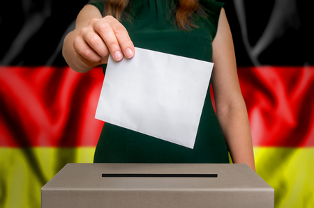 Election in Germany - voting at the ballot box. The hand of woman putting her vote in the ballot box. Flag of Germany on background.