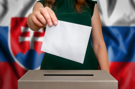 Election in Slovakia - voting at the ballot box. The hand of woman putting her vote in the ballot box. Flag of Slovakia on background.