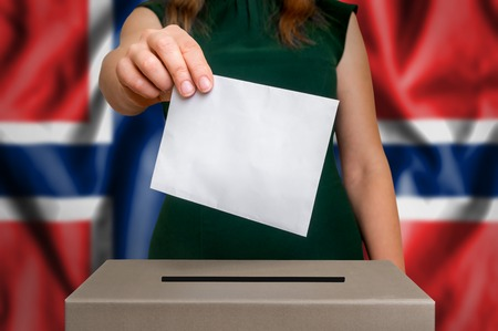Election in Norway - voting at the ballot box. The hand of woman putting her vote in the ballot box. Flag of Norway on background.