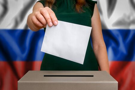 Election in Russia - voting at the ballot box. The hand of woman putting her vote in the ballot box. Flag of Russia on background.