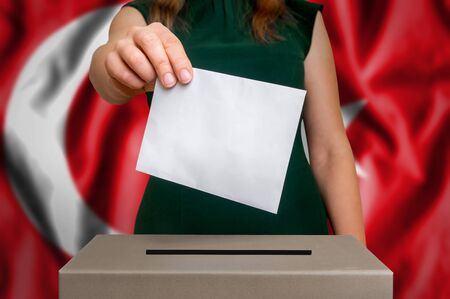 Election in Turkey - voting at the ballot box. The hand of woman putting her vote in the ballot box. Flag of Turkey on background.