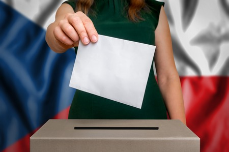 Election in Czech Republic - voting at the ballot box. The hand of woman putting her vote in the ballot box. Flag of Czech Republic on background. Stock Photo