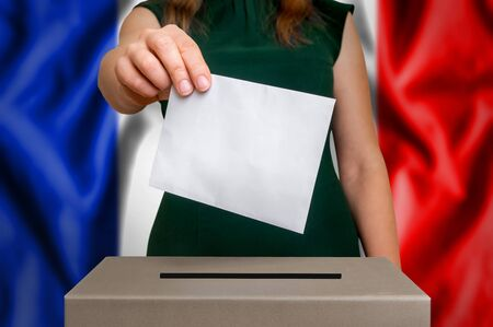Election in France - voting at the ballot box. The hand of woman putting her vote in the ballot box. Flag of France on background. Stock Photo