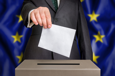Election in European Union - voting at the ballot box. The hand of man putting his vote in the ballot box. Flag of EU on background. Stock Photo