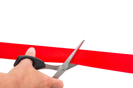 Hand with scissors cutting red ribbon - opening ceremony concept. Isolated on white background