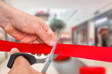 Hand with scissors cutting red ribbon - opening ceremony concept