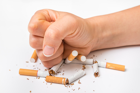 Human fist and pile of broken cigarettes, nicotine addiction - stop smoking concept