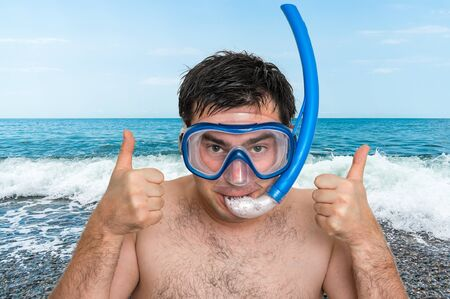 Man with snorkeling mask for diving stands on beach in front of the sea