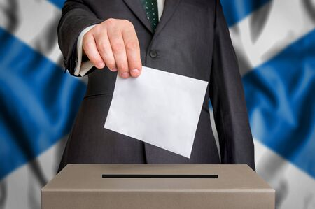 Election in Scotland - voting at the ballot box. The hand of man putting his vote in the ballot box. Flag of Scotland on background.