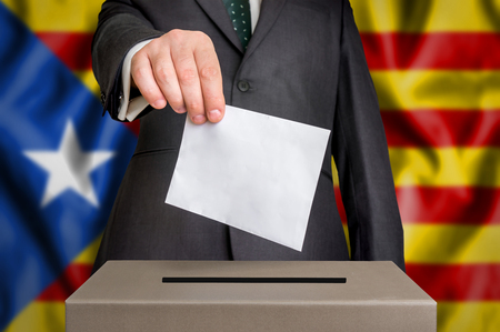 Election in Catalonia - voting at the ballot box. The hand of man putting his vote in the ballot box. Flag of Catalonia on background.