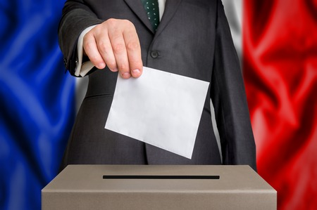 Election in France - voting at the ballot box. The hand of man putting his vote in the ballot box. Flag of  on background. Stock Photo