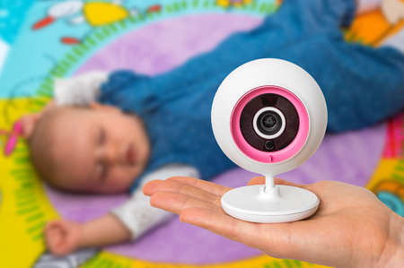 Hand of mother is holding baby monitor camera for safety of her cute baby Stock Photo