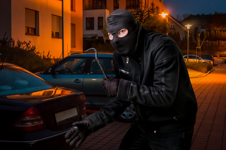 Masked thief in balaclava with crowbar wants to rob a car at night